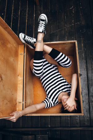 striped pajamas: Girl in striped bodysuit lying in wooden box Stock Photo