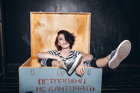 striped pajamas: Girl wearing striped pajamas sitting in wooden box