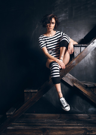 striped pajamas: Girl in a striped pajamas against the black wall Stock Photo