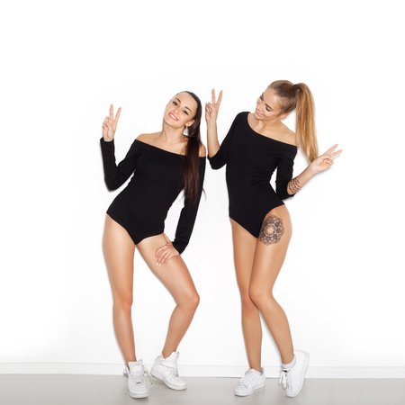 Two young girl friends standing together and having fun. Showing signs with their hands.