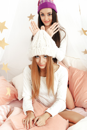 teen girl underwear: Two girls having fun in bedroom. Blonde woman and brunette lady smiling Stock Photo