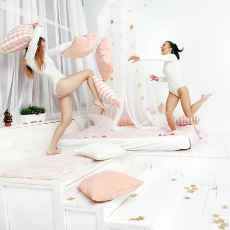 pelea: felices muchachas de risa que tienen una pelea de almohadas en la cama en su casa