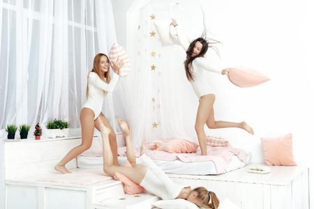 lesbianas: amigos felices o adolescentes que se divierten y pelea de almohadas en la cama en su casa