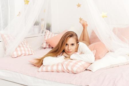 mujer en la cama: enfoque selectivo en la hermosa mujer sonriente con un pijama blanco acostado en la cama que nos mira a pensar en velada milagro.