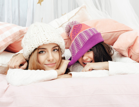 teen girl underwear: Two girls in bedroom. Blonde woman and brunette lady smiling Stock Photo