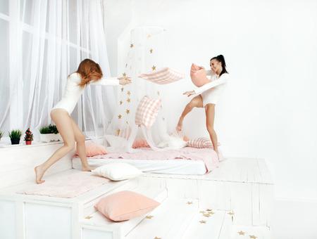 femmes souriantes: amis heureux ou les adolescentes ayant combat amusant et un oreiller sur le lit à la maison