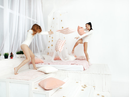 nightwear: happy friends or teenage girls having fun and pillow fight on bed at home