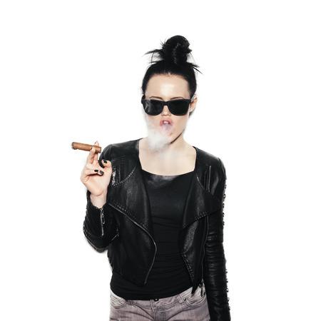 cigarro: Mujer atractiva en gafas de sol que sopla el humo de un cigarro. chica de estilo botín en fondo blanco, no aislado Foto de archivo