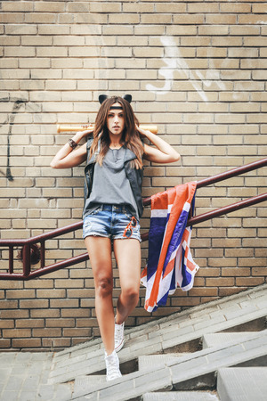 british girl: Bad girl with baseball bat and British flag at street. Urban scene. Outdoor lifestyle portrait Stock Photo