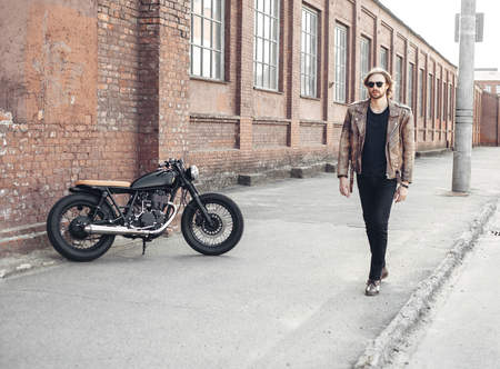 trend: portrait young guy with a beard and mustache with sunglasses and white T-shirt posing on the street vintage man, fashion men, hipster street casual a motorcycle