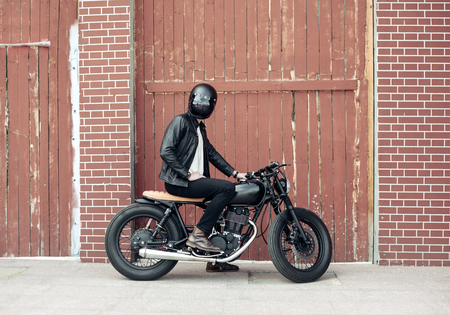 Biker sitting on vintage custom motorcycle. Outdoor lifestyle portrait