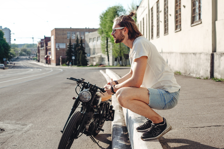 casual men: portrait young guy with a beard and mustache with sunglasses posing on the street vintage man, fashion men, hipster street casual motorcycle