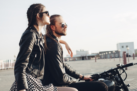 sexy couple embrace: fashion couple sitting on a motorcycle at sunset. young man and woman with vintage custom motorcycle