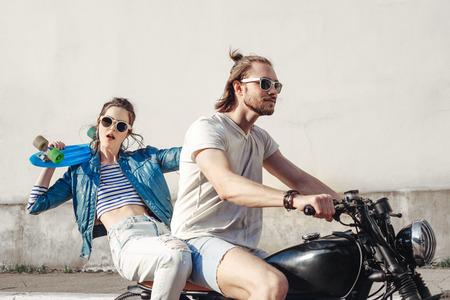 若い女性モデルの持株のスケート ボード。若い男性と女性の晴れの日に楽しんで 写真素材
