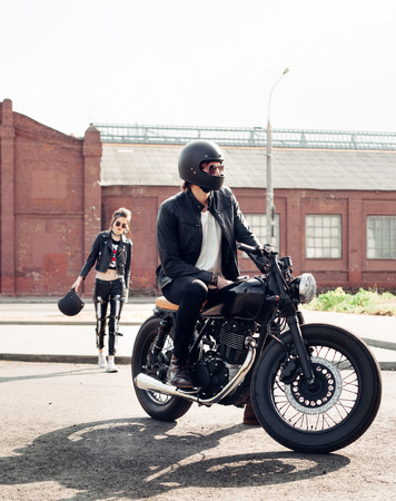 a helmet: Couple in love. Bikers and vintage custom motorcycle. Outdoor lifestyle portrait