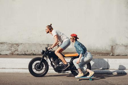 Jongeren skateboarden samen op weg. Jonge man en vrouw rijden op een zonnige dag. Stockfoto