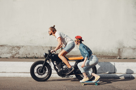 Young people skateboarding together on road. Young man and woman riding on a sunny day.