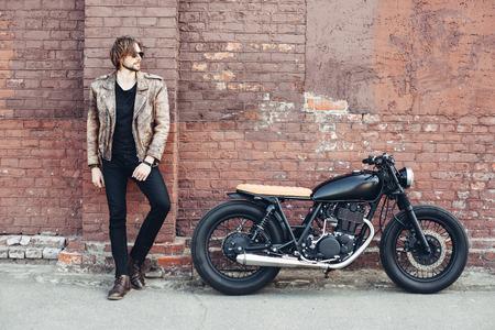 Porträt junger Mann mit einem Bart und Schnurrbart mit Sonnenbrille und weißem T-Shirt auf der Straße Vintage-Mann posiert, Mode für Männer, hipster Straße lässig ein Motorrad