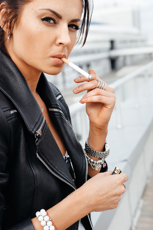 Outdoors lifestyle portrait of young brunette woman smoking a cigarette Фото со стока