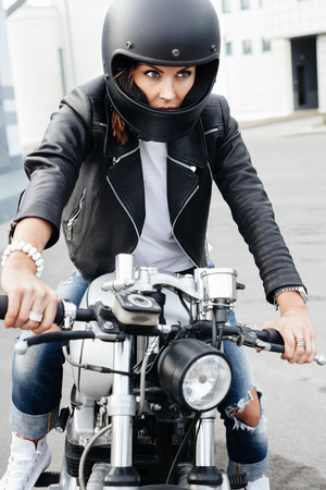 Biker girl in helmet on vintage custom motorcycle