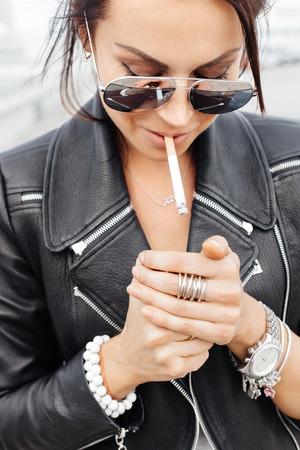 chica fumando: retrato estilo de vida al aire libre de la mujer atractiva joven que enciende un cigarrillo