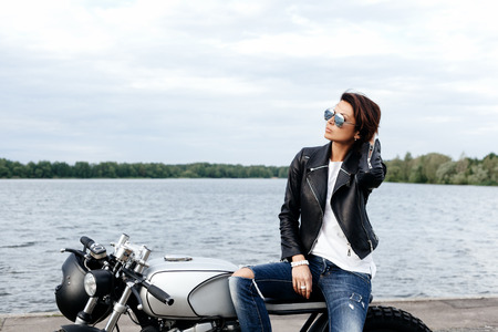 Biker girl in a leather jacket on the vintage custom motorcycle on the background of the lake Stock Photo