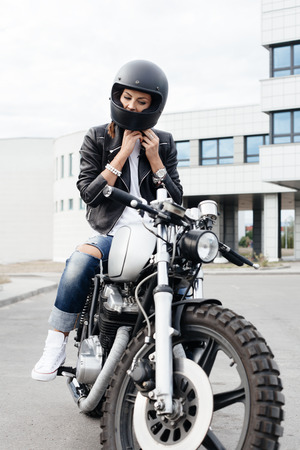 casco moto: Outdoor lifestyle portrait of biker girl sits on vintage custom motorcycle and buttons helmet