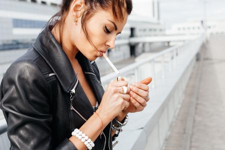 Outdoors lifestyle portret van een jonge vrouw die een sigaret rookt Stockfoto