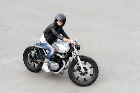 casco moto: retrato estilo de vida al aire libre de la motociclista sentado en una motocicleta de encargo de la vendimia Foto de archivo