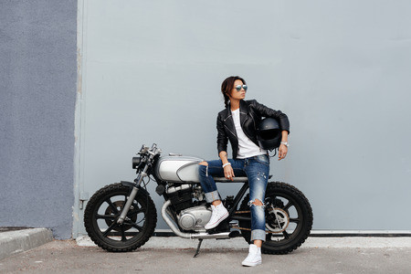 Outdoor lifestyle portrait of sexy biker girl sitting on a vintage custom motorcycle