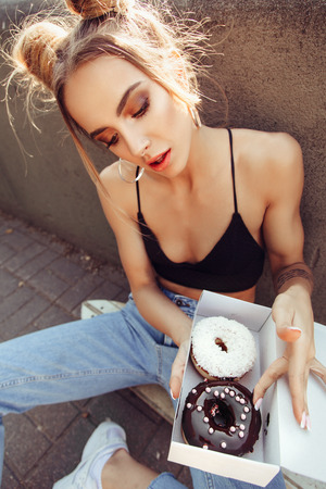 woman eating cake: Portrait of cute young girl holding box of donuts