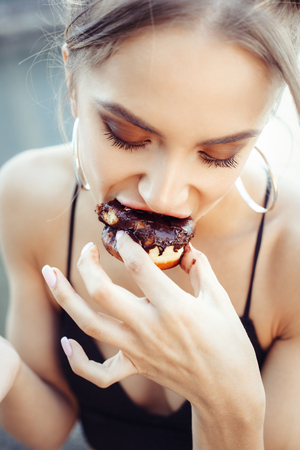 woman eating cake: Portrait of hungry young beautiful girl eating donut Stock Photo