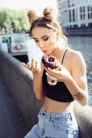 hungry: Portrait of funny beautiful girl eating donut. Hungry woman licking fingers
