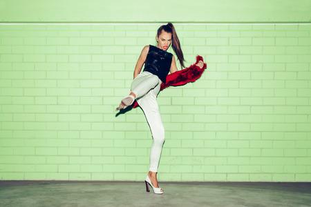 urban fashion: Portrait of fashion Girl having fun at the Green Brick Wall Background. Urban Fashion Concept