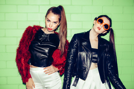 Two young naughty fashion girls posing on a background of green brick wall Standard-Bild
