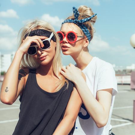 urban people: Two beautiful happy girls in sunglasses on the urban background. Young active people. Outdoors Stock Photo