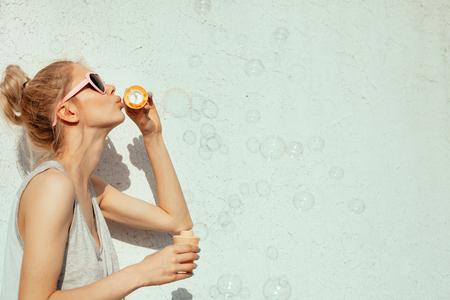 Im Freien Lifestyle-Portrait des netten Mädchens bläst Seifenblasen