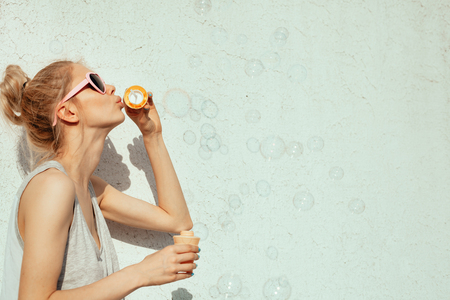 Outdoors lifestyle portrait of cute girl blowing soap bubbles