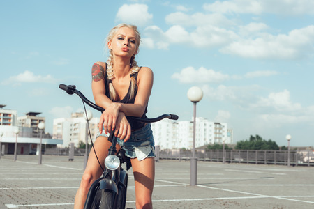 cruiser bike: beautiful fashion girl with bicycle in city. Soft sunny color outdoors portrait