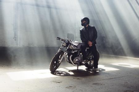 Sexy biker man wearing jeans and leather jacket sitting on vintage custom motorcycle. Urban scene