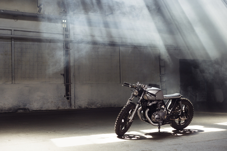 industrial design: Vintage motorcycle standing in a dark building in the rays of sunlight. Side view