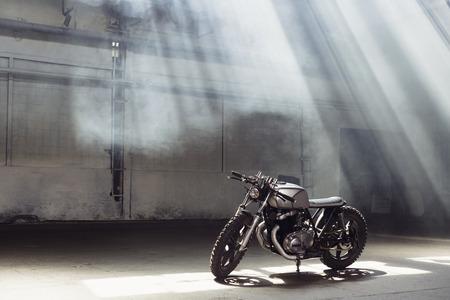 Motocicleta de la vendimia que se coloca en un edificio oscuro en los rayos de la luz del sol. Vista lateral Foto de archivo - 63592763