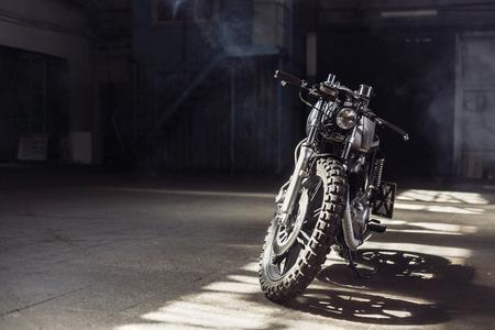 빈티지 오토바이 햇빛의 광선에 어두운 건물에 서 서. 톤된 색상입니다. 전면보기