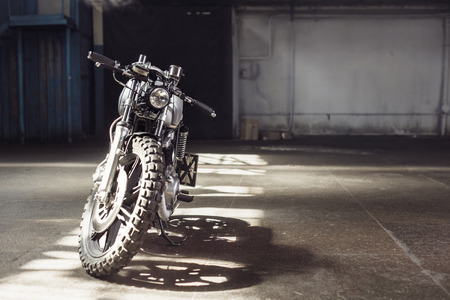 Vintage motorcycle standing in a dark building in the rays of sunlight. Front view