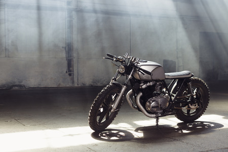 Vintage motorcycle standing in a dark building in the rays of sunlight