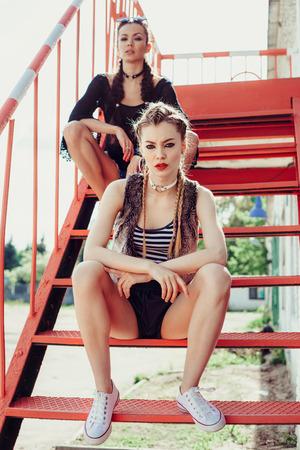 Dos muchachas frescas jóvenes sentados en las escaleras en un día soleado. estilo de moda, peinado con trenzas. retrato estilo de vida al aire libre