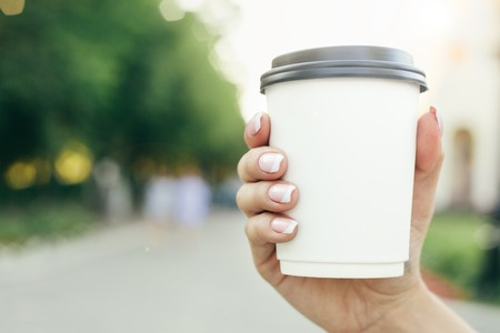 hand holding paper cup of coffee on natural morning background. Horizontal view