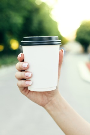Ruka držící papírový šálek kávy na přírodním ranním pozadí. Horizontální pohled