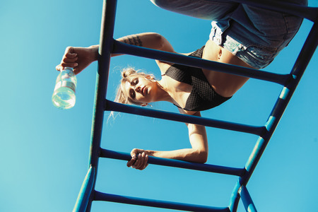 girl working out: Active young woman exercising on ladder. Sporty fit girl working out at outdoor gym and drinking water