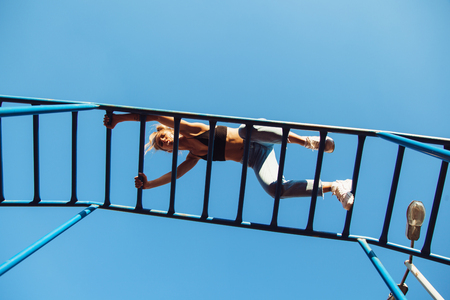 girl working out: Active young woman exercising on ladder. Sporty fit girl working out at outdoor gym
